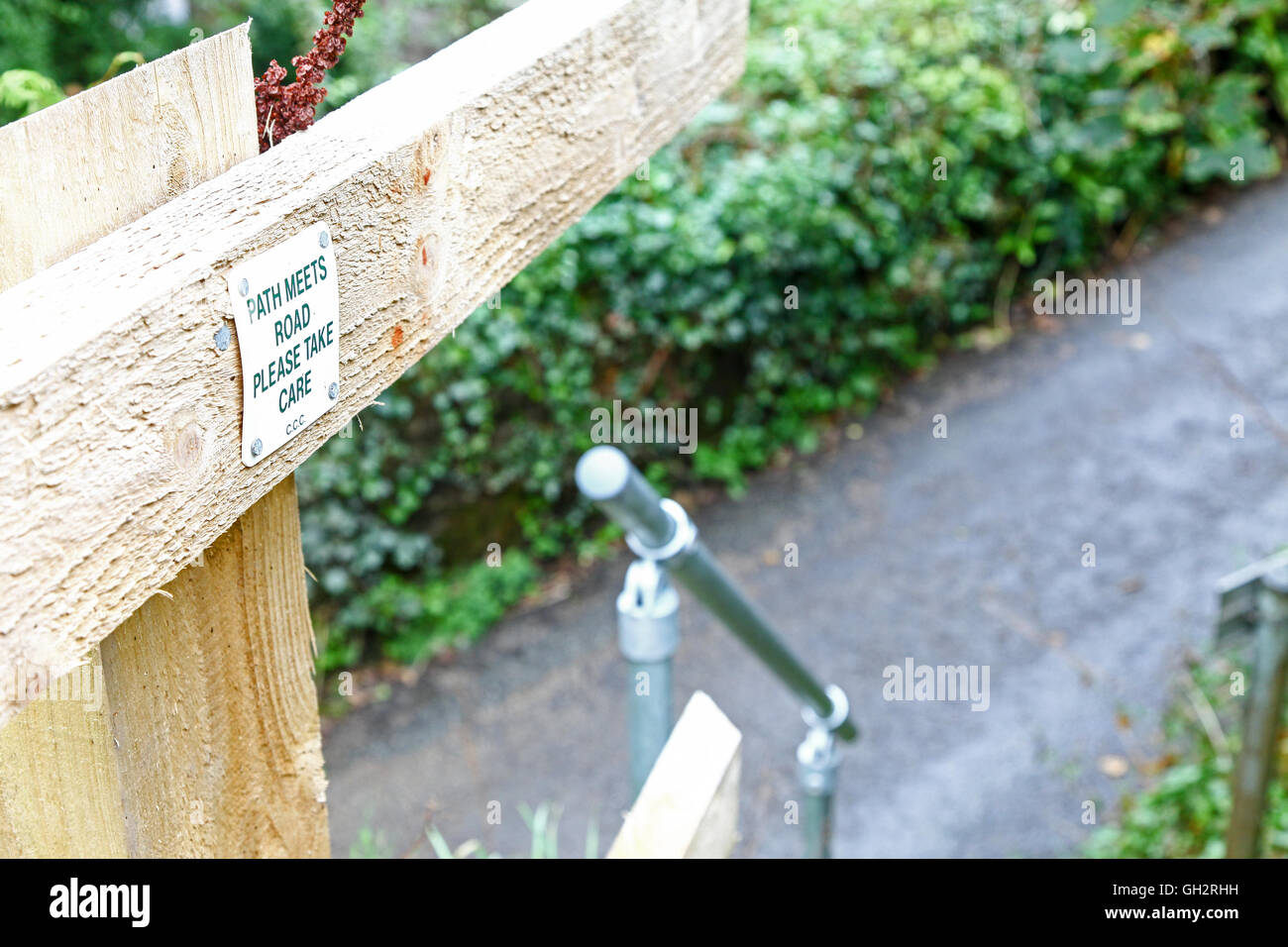 A sign saying 'path meets road, take care' on some steps leading down to a road - Stock Image