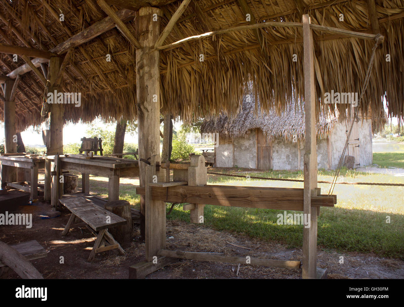 Pole lathe and other replica tools under a Timucua-style palm frond hut.  The Fountain of Youth Park, St. Augustine - Stock Image
