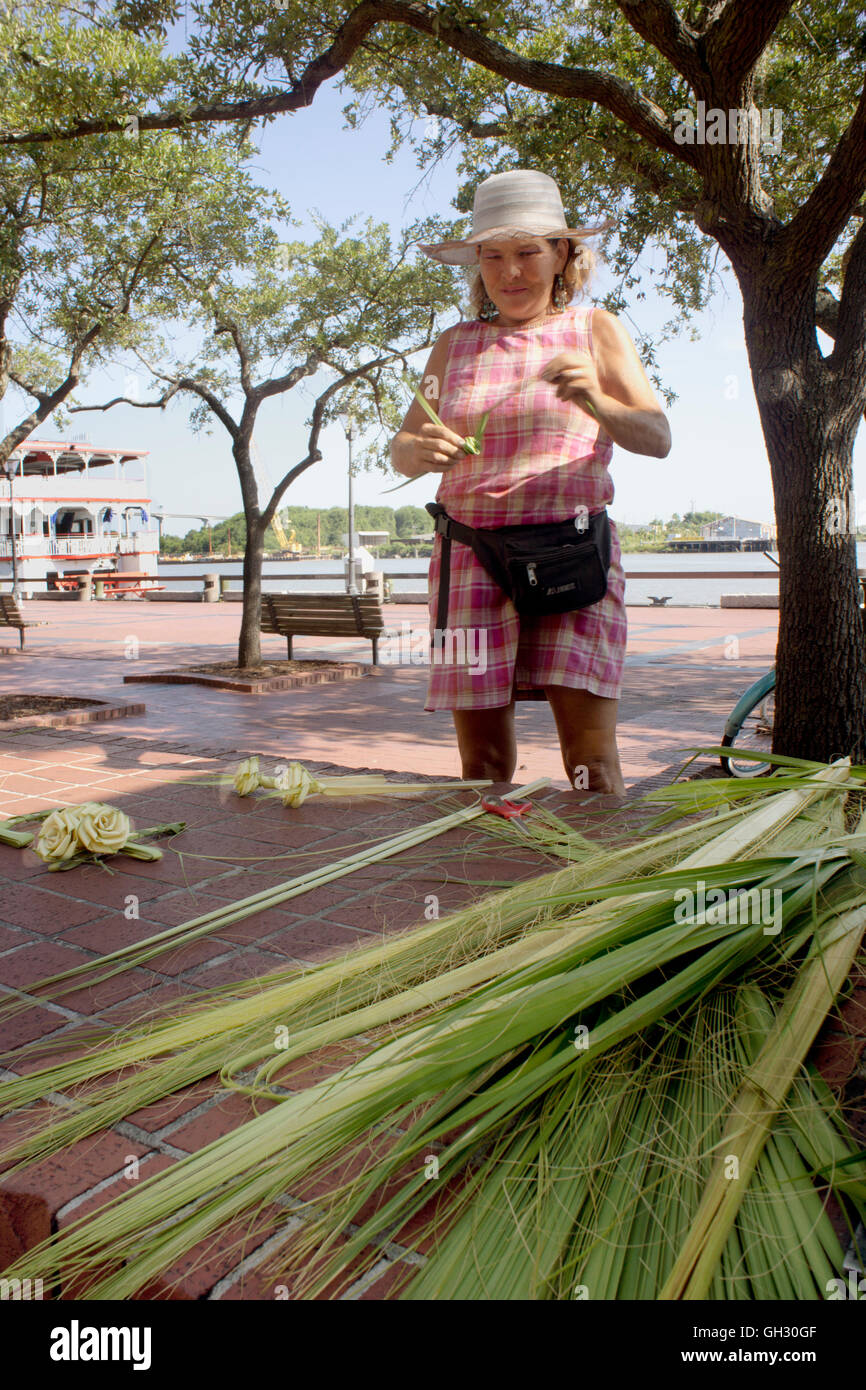 Savannah native crafting palm frond roses on the historic riverfront. Stock Photo