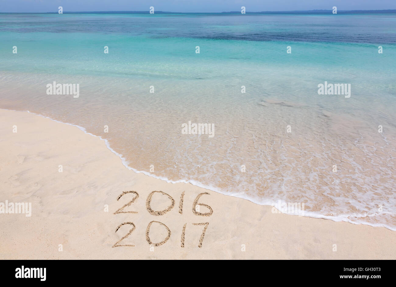 Years 2016 and 2017 are inscribed on sandy beach - Stock Image