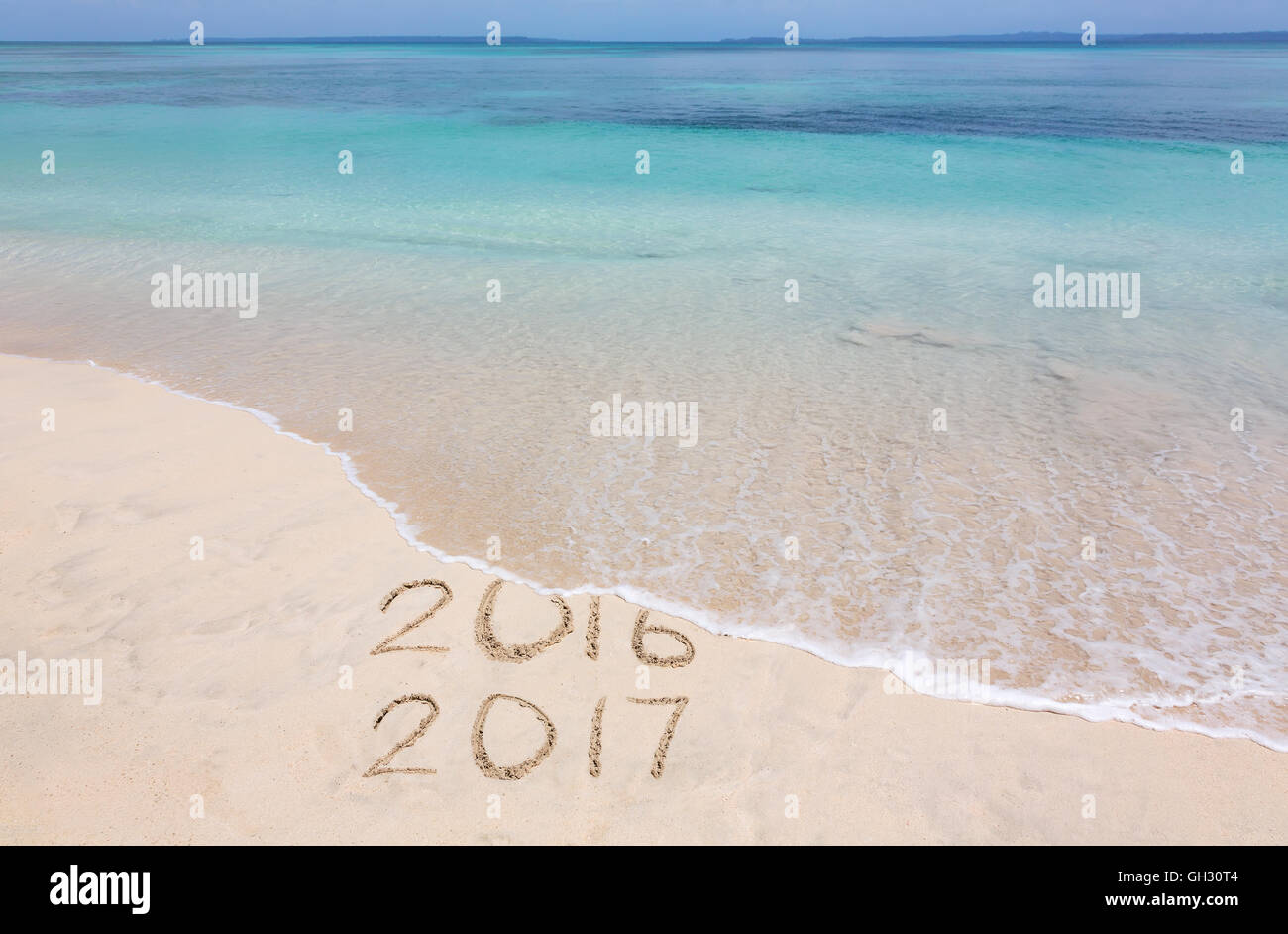 Year 2016 is washed away by ocean wave - Stock Image