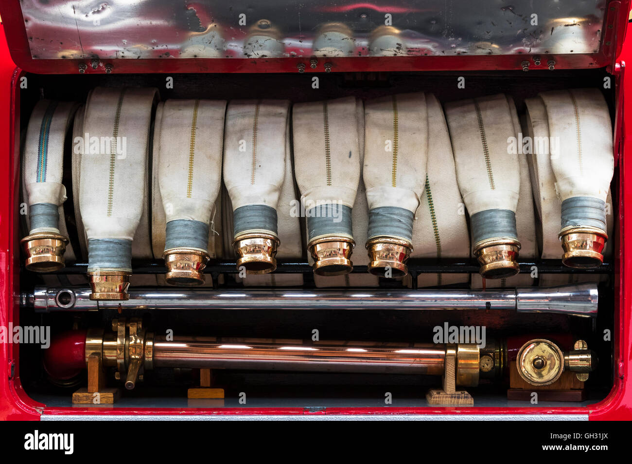 Canvas hoses and brass coupling on a 1937 vintage Fire engine - Stock Image
