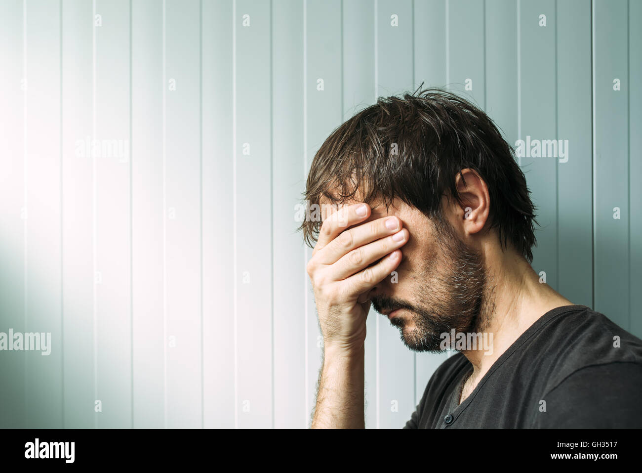 Profile portrait od miserable troubled man with serious expression, depressive male with hand on face. - Stock Image