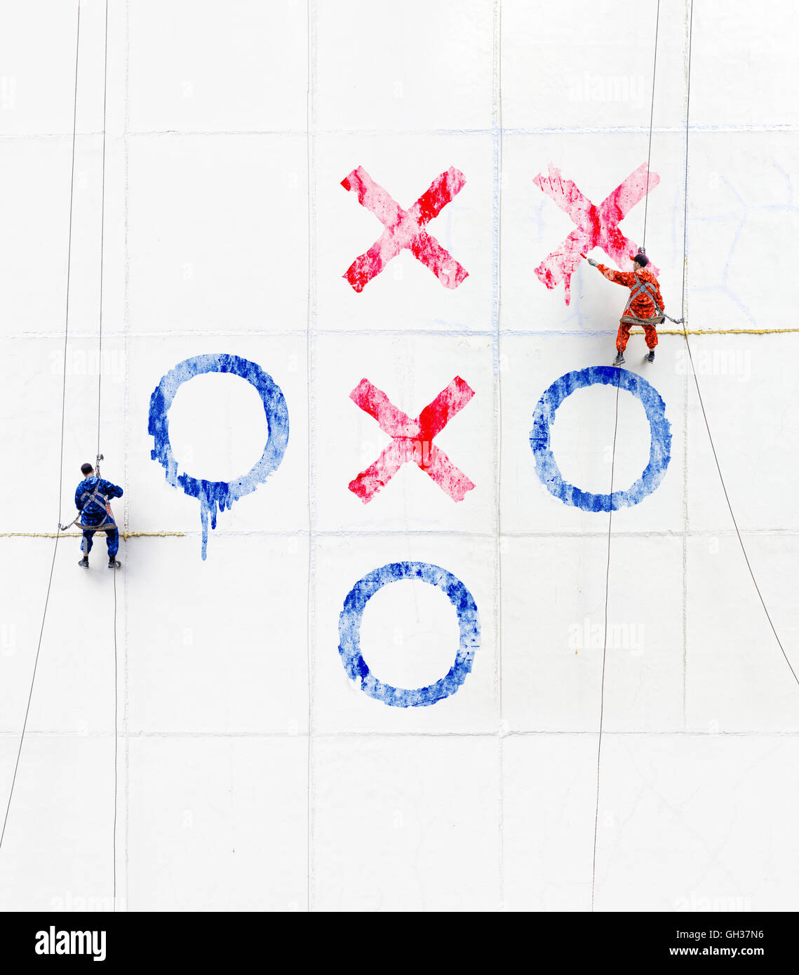 Maintenance workers  play tick-tack-toe  outside a wall - Stock Image