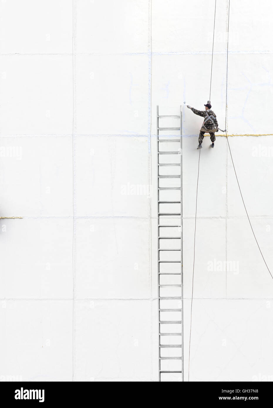 Maintenance worker climbing outside a wall - Stock Image