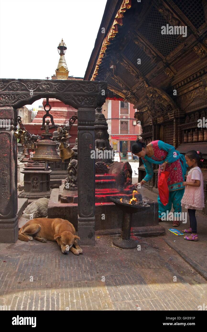 Mother and daughter at Hindu shrine with sleeping dog at Swayambhunath Stupa or Monkey Temple, Kathmandu, Nepal, - Stock Image