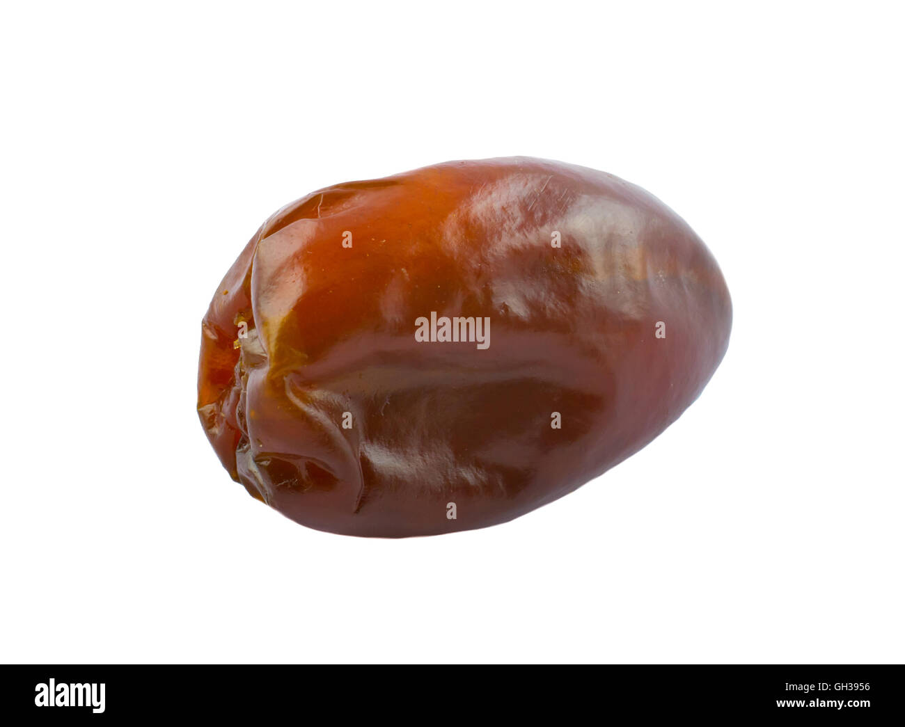 A golden brown date isolated on a white background - Stock Image