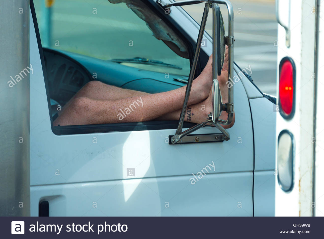 Summer scene: Young man sticking his legs out of the car's window due to the hot weather. - Stock Image