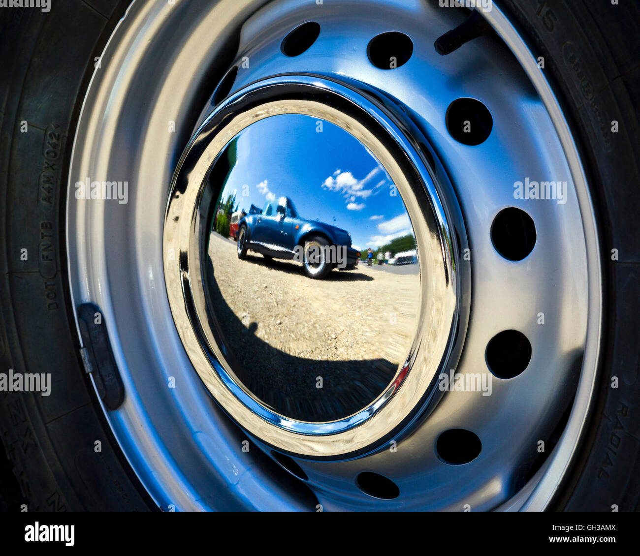 Reflection of a vintage car in the wheel cover of another vintage ...