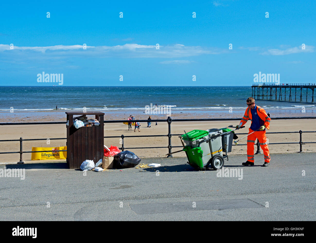 Council workman approaching overflowing rubbish bin on the promenade at Saltburn, North Yorkshire, England UK - Stock Image