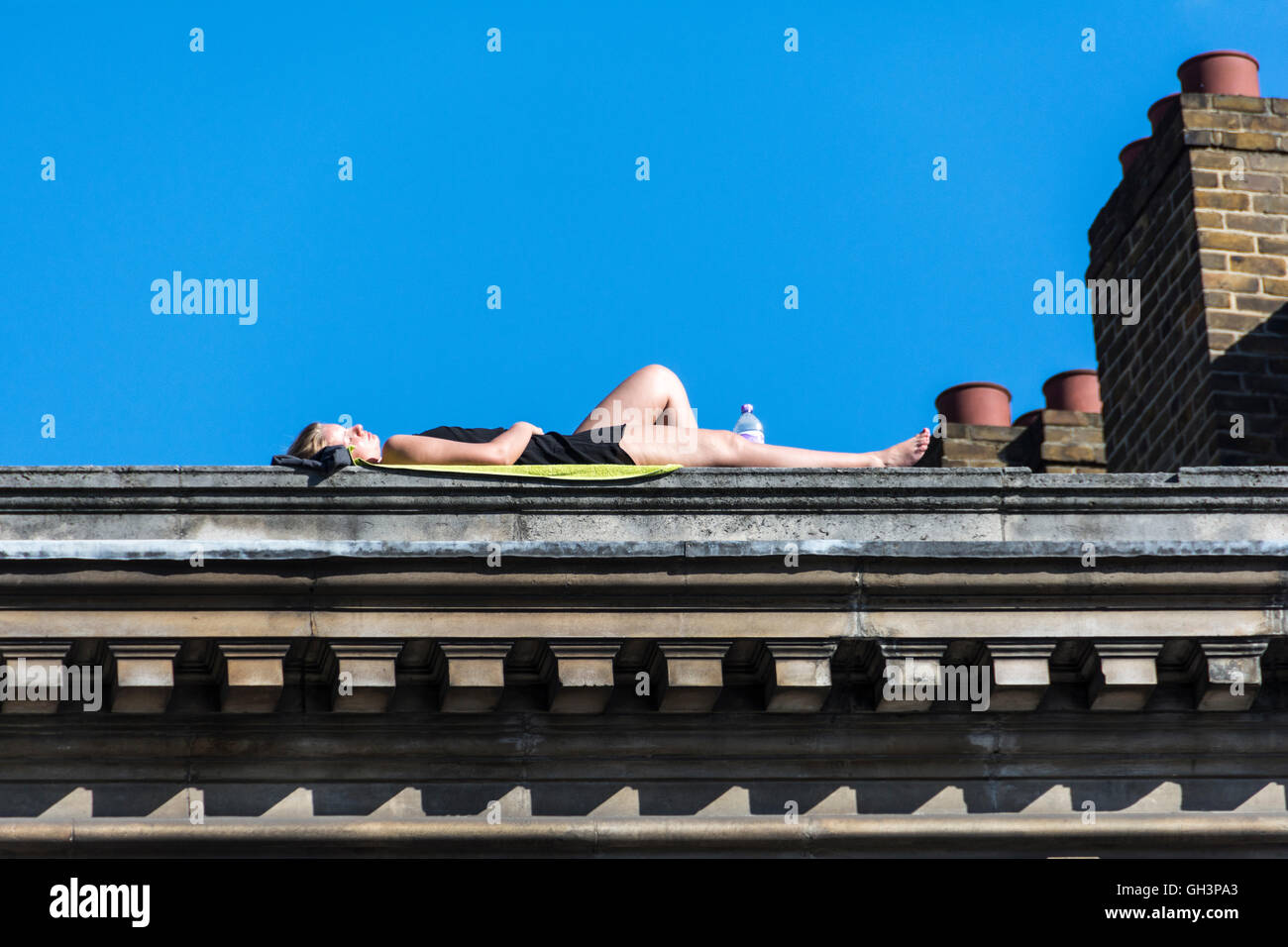 London, England, UK: A woman sunbathing on top of a roof near Borough Market in Southwark. - Stock Image