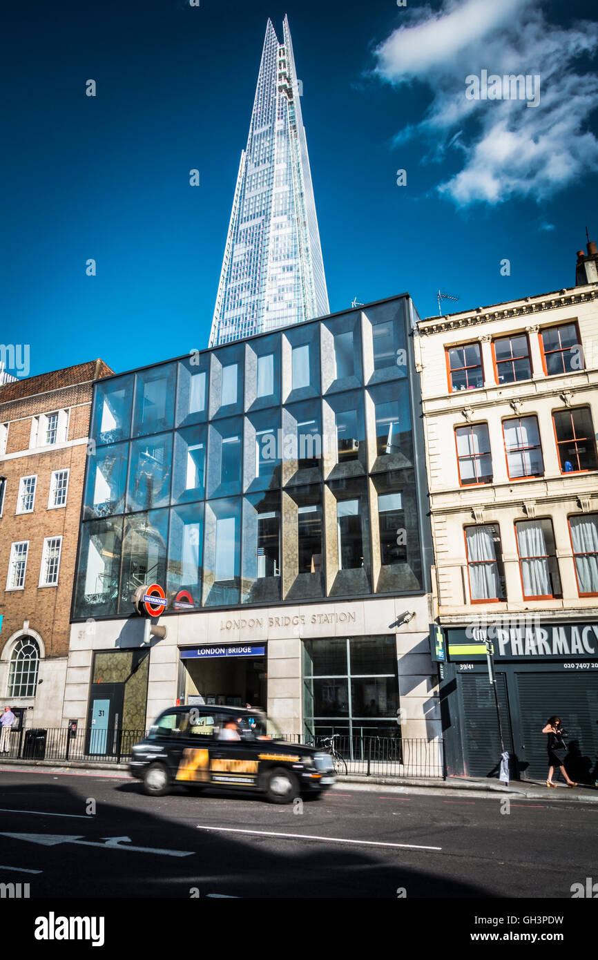 London, England, UK: A couple walking in the sun near the Shard in Southwark. - Stock Image