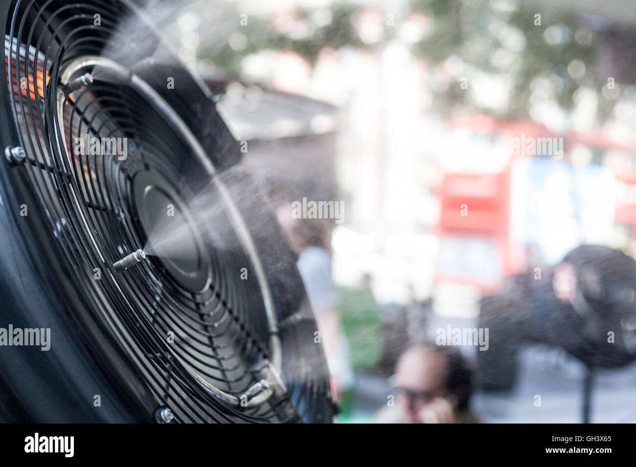 Fan sprinklers splashing vaporized water at terrace bar in order to cool the hot summer temperature in Spain - Stock Image