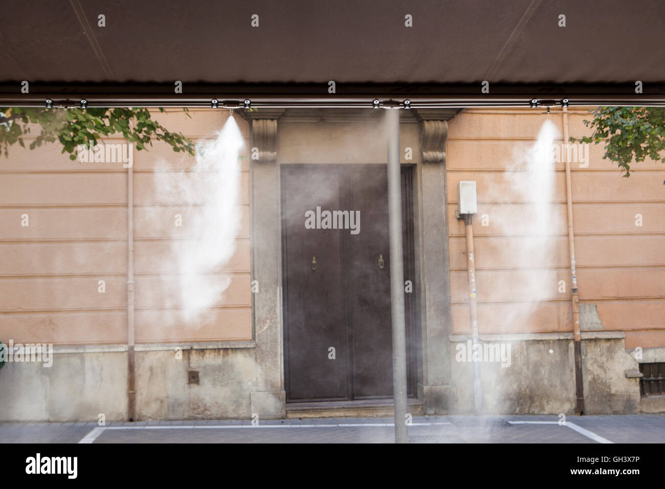 Awning sprinklers splashing vaporized water at terrace bar in order to cool the hot summer temperature in Spain - Stock Image