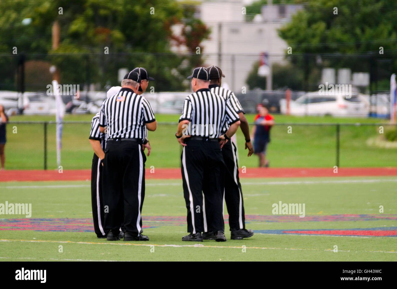 Referees discussing a play during high school football game - Stock Image