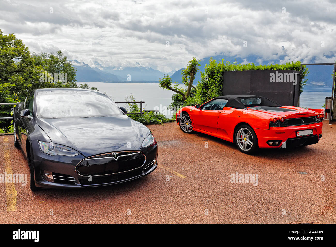 A  Tesla S Electric Sedan and a Red Ferrari Convertible Car Parked in a Scenic Overlook of Lake Geneva, Chebrex, - Stock Image