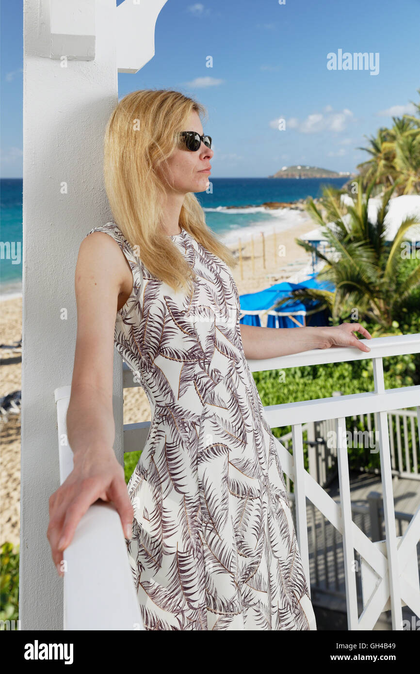 Portrait View of a Blond Woman in A Summer Dress Standing on a Balcony of a Beach Resort and Relaxing, Frenchman's - Stock Image