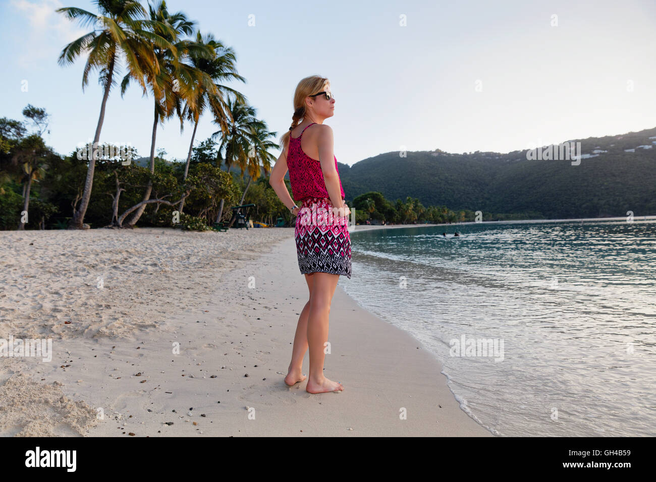 Low Angle View Of a Woman Standing on a Caribbean Beach Barefoot in a Summer Dress at Sunset Hour, Magens Bay, St Stock Photo