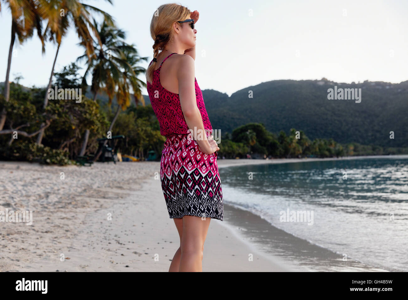 Low Angle Close Up View of a Woman in Sundress on A Beach Looking Out, Magens Bay, St Thomas, US Virgin Islands - Stock Image