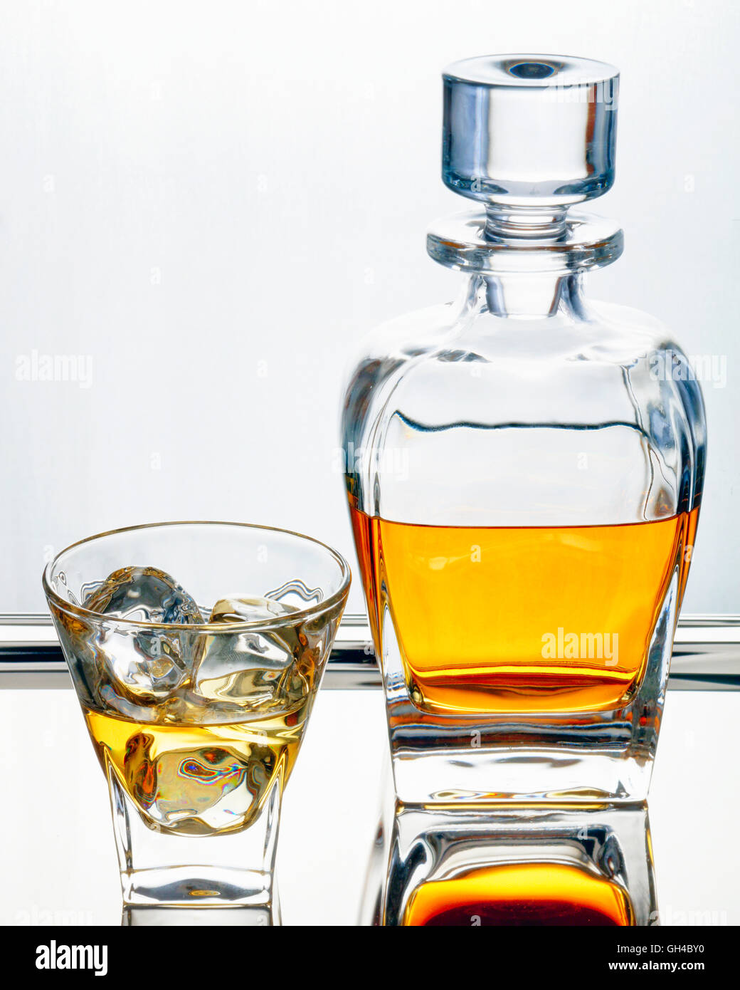 Smooth Scotch Whiskey in Traditional Decanter and Glass with Ice Cubes - Stock Image