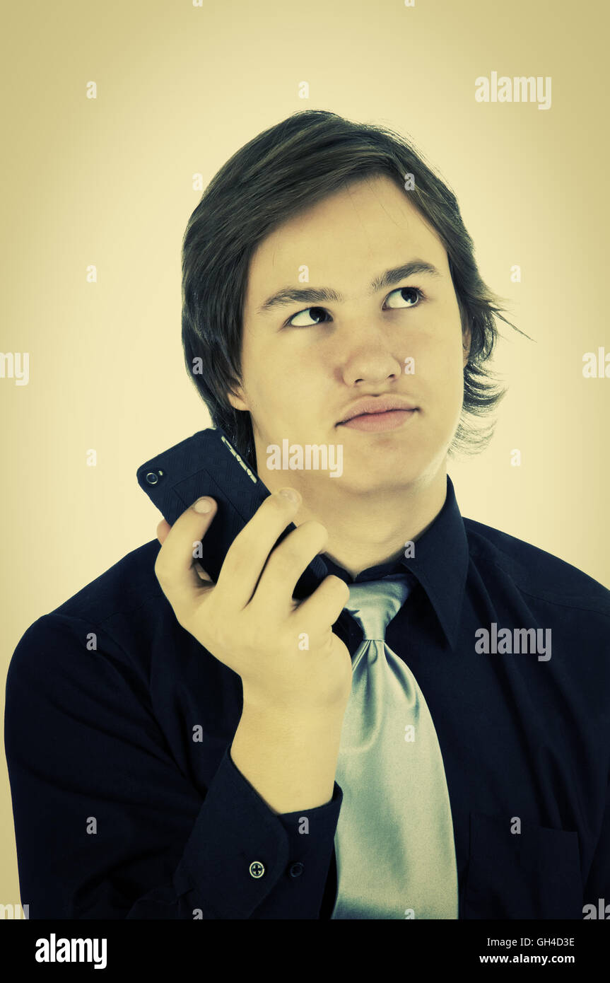 Young man rolling his eyes as a result of miscommunication on his cellphone. Retro instagram look. - Stock Image