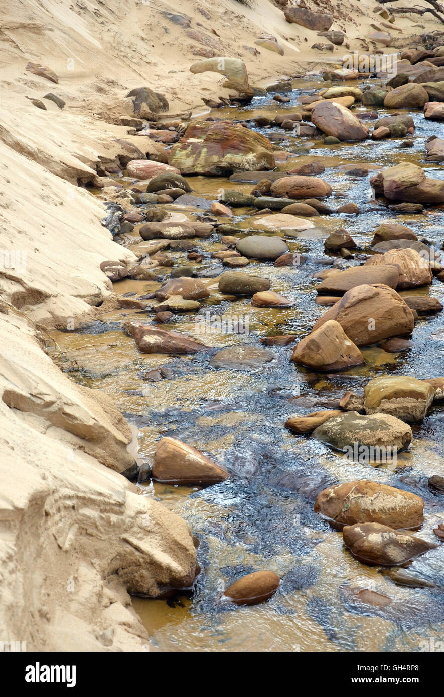 Sandstone boulders in a sandy flowing freshwater creek Stock Photo