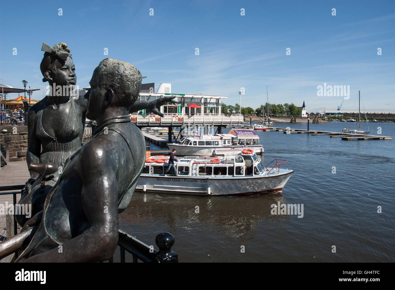 Bronze Statue 'People Like Us' by John Clinch overlooks the Inner Harbour at Cardiff Bay - Stock Image