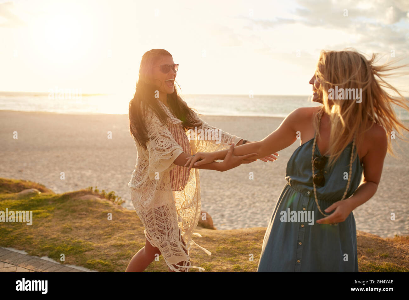 Two young female friends on a sidewalk along the beach playing. Young women having fun on the sea shore, enjoying - Stock Image