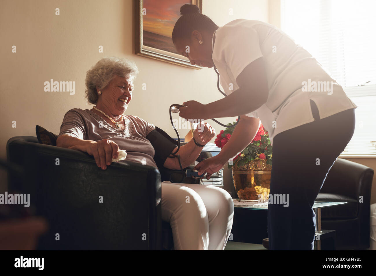 Nurse measuring blood pressure of senior woman patient in retirement home. Home caregiver doing routine checkup - Stock Image