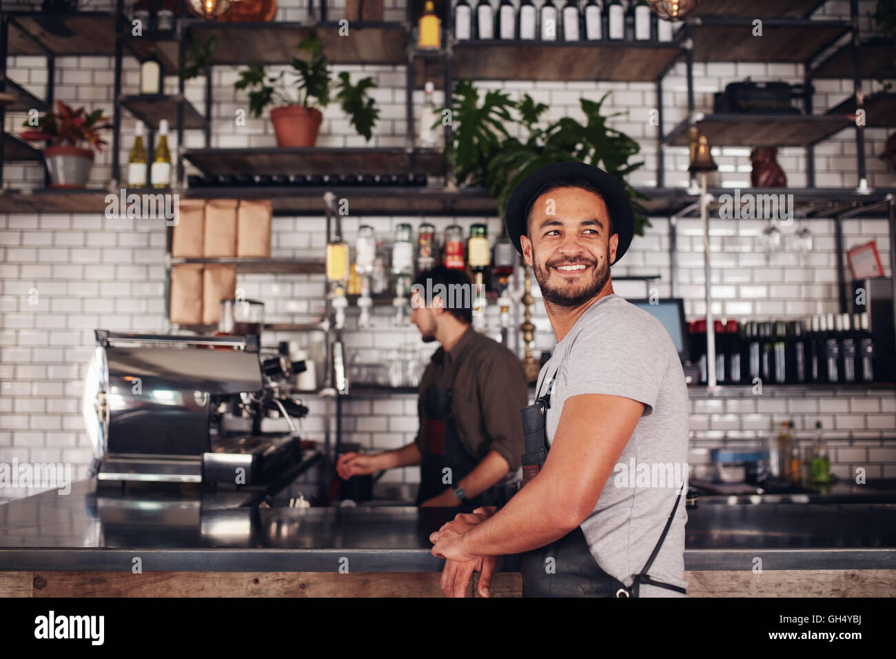 Coffee shop owner standing with barista working behind the counter making drinks. - Stock Image