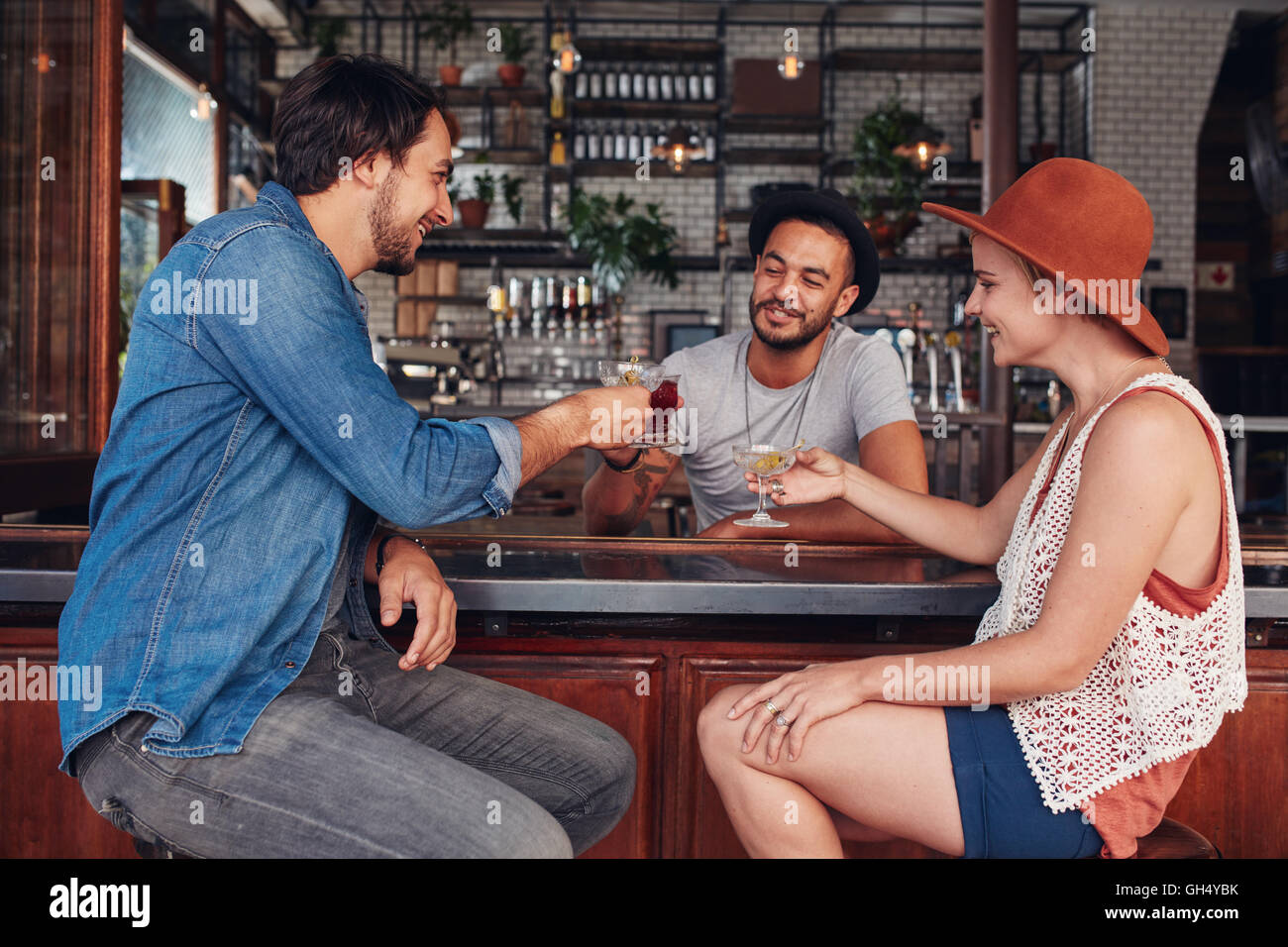 Portrait of young modern people sitting in the coffee shop and having their drinks. Group of friends at a cafe toasting - Stock Image