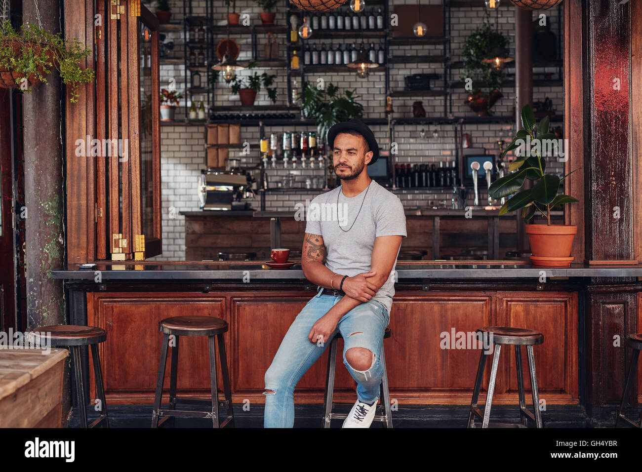 Portrait of upset young man sitting alone at a cafe counter. Modern young caucasian man looking serious. - Stock Image