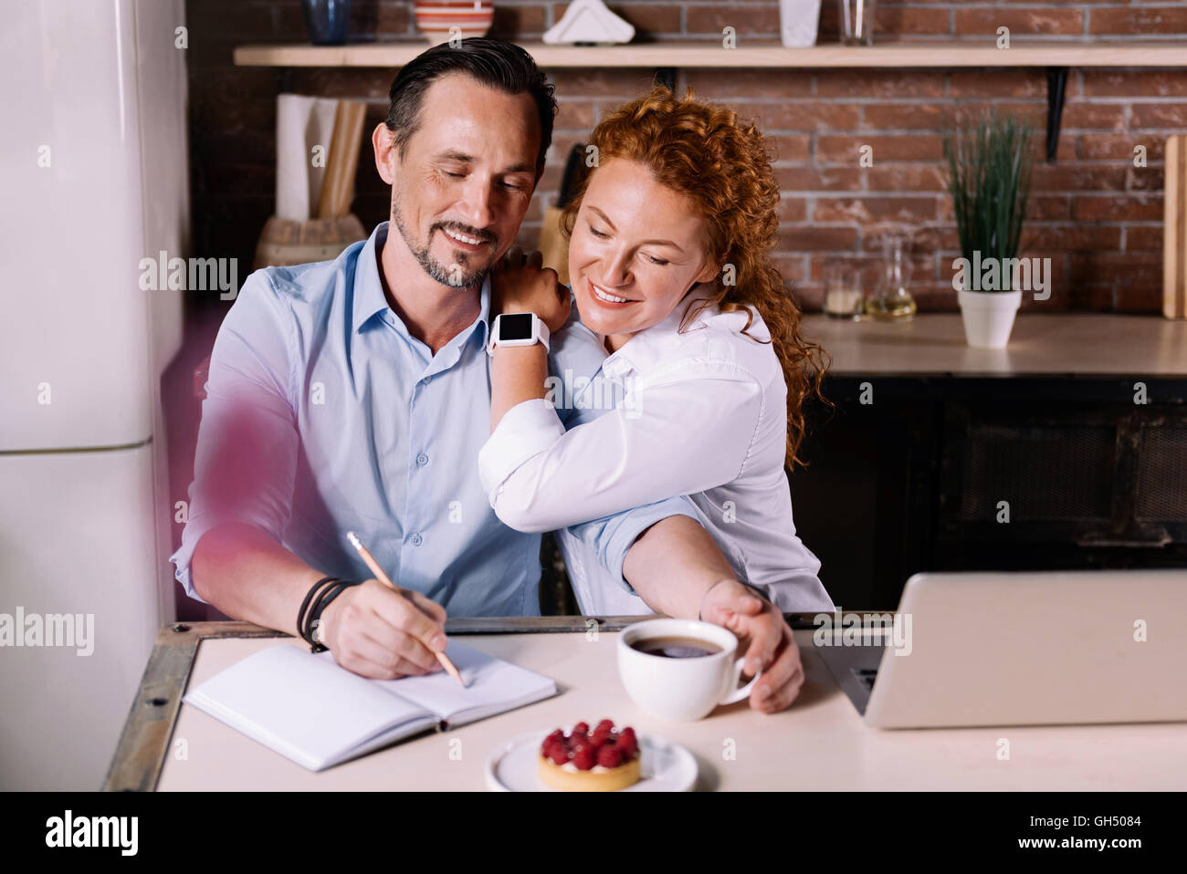 Woman looking how man writing - Stock Image