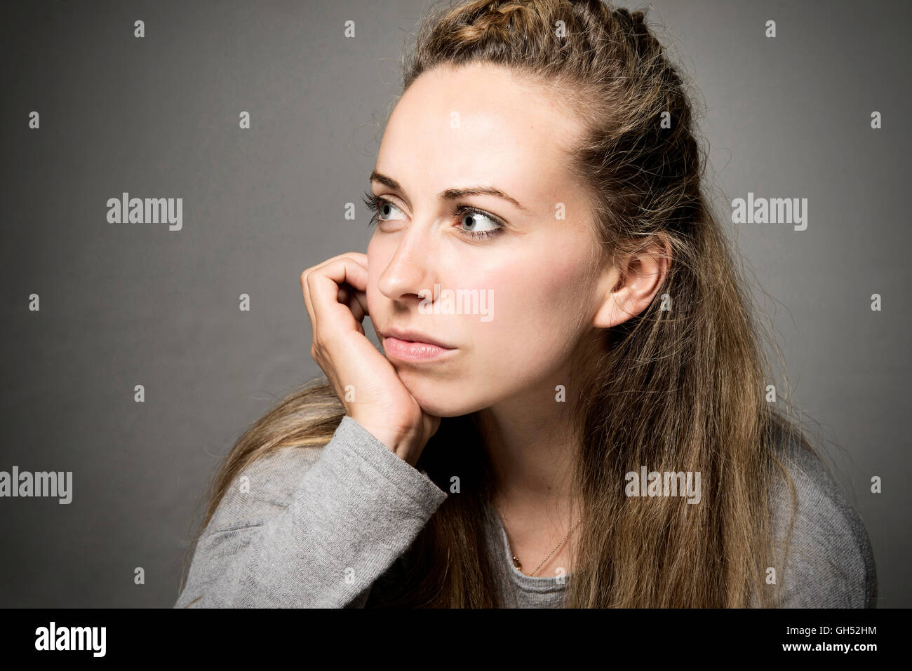 Young woman close up looking sorrowful, sad, thoughtful hand on chin looking in to the distance - Stock Image