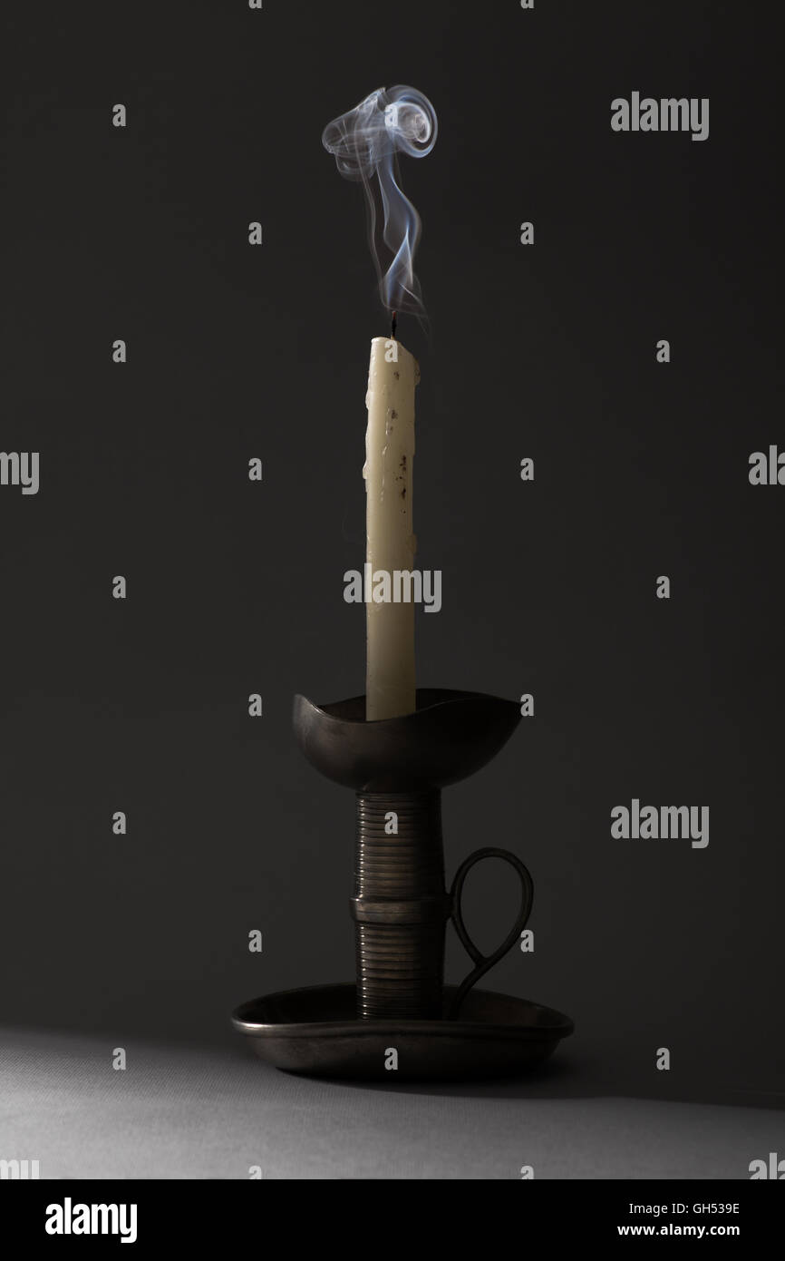 Blown Out Smoking Candle on Iron Candlestick - Stock Image