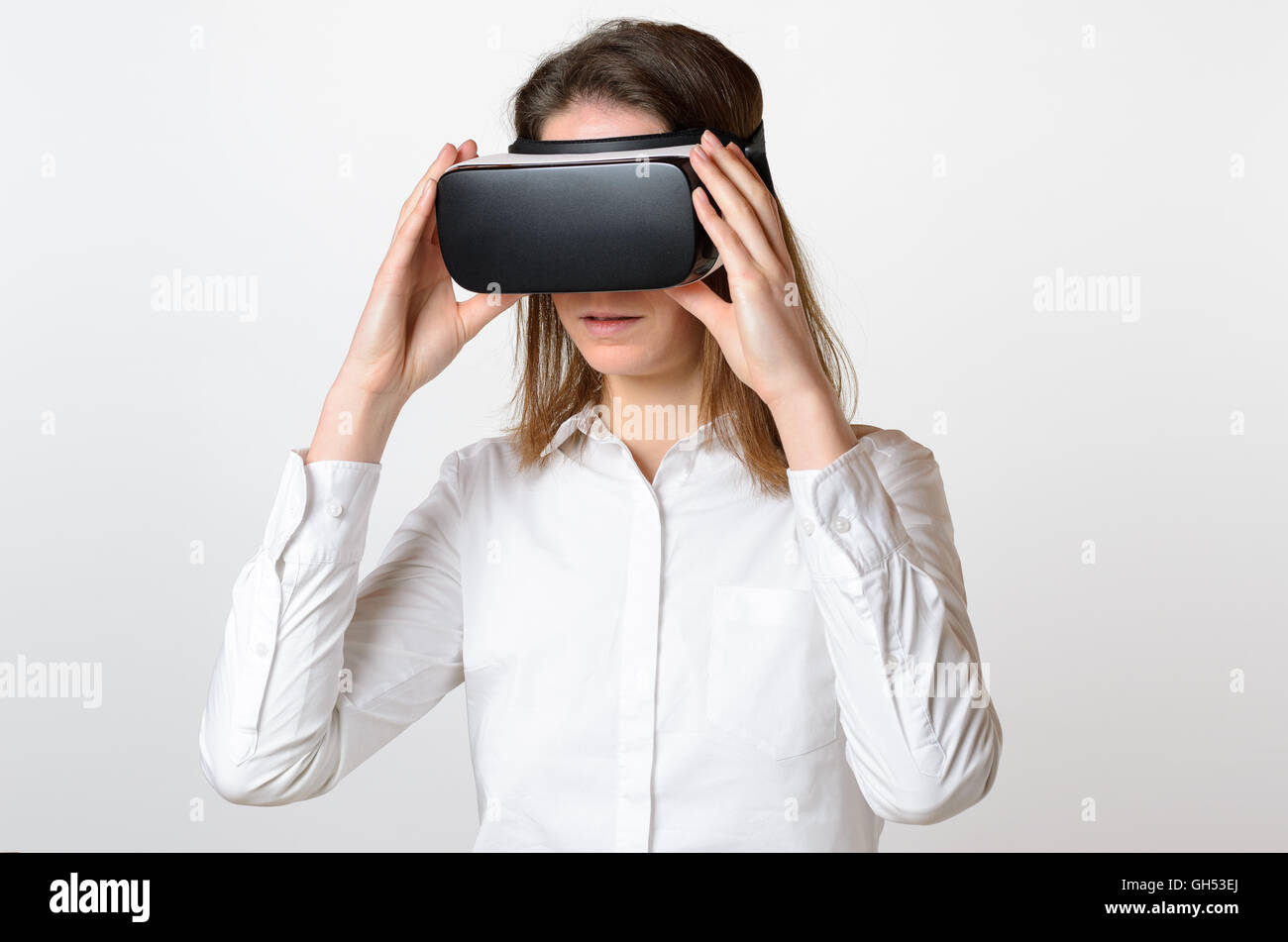 Single serious young woman in dark hair holding large 3D virtual reality viewing device over face on gray background - Stock Image