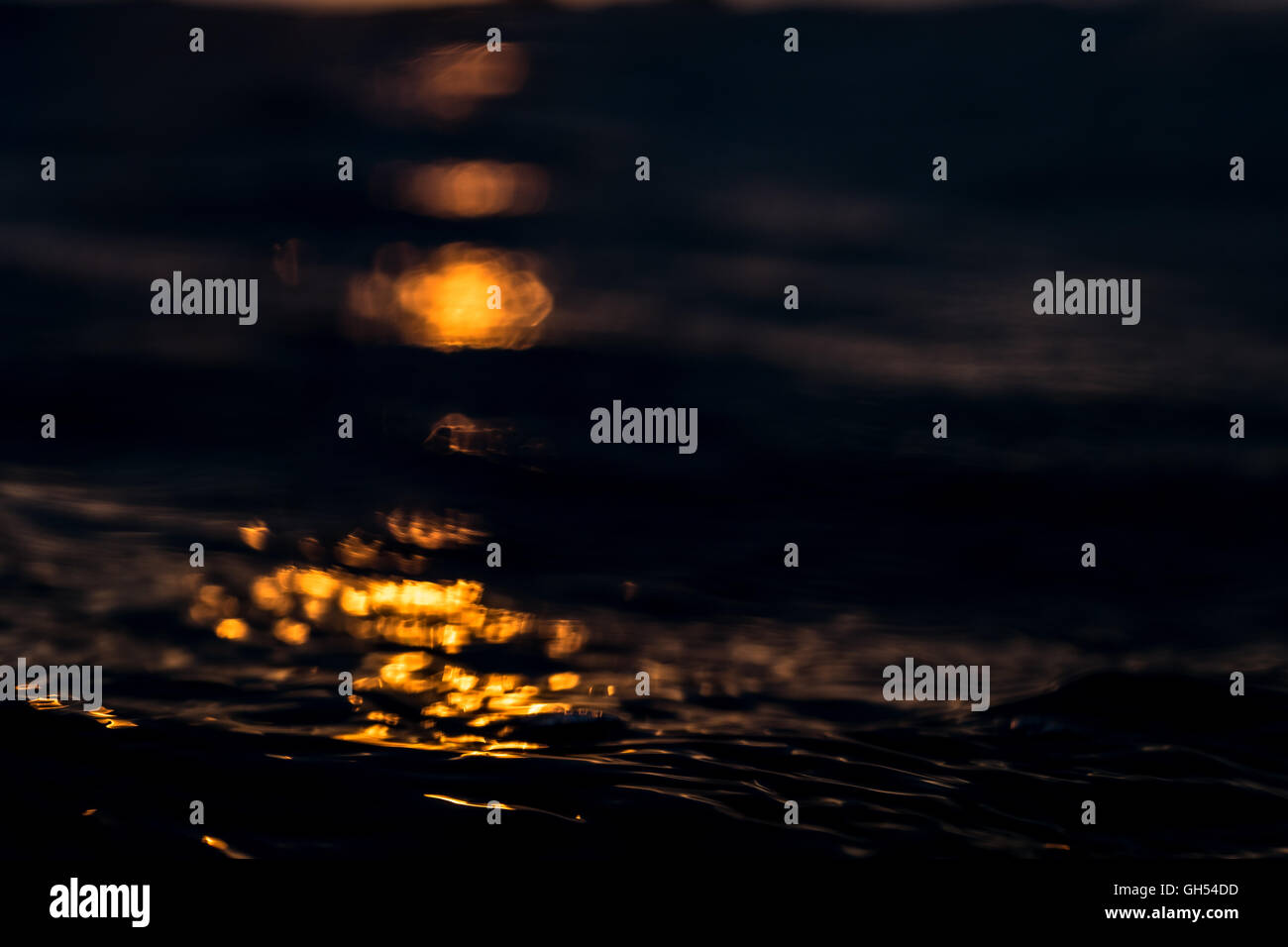 Reflection of the sunset on the ocean surface - Stock Image