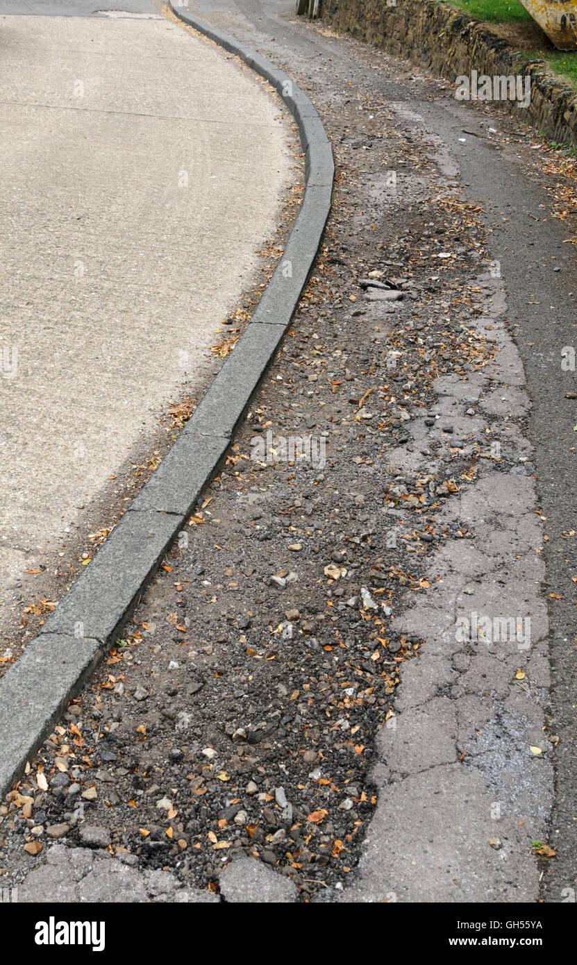 Cracked and damaged pavement - Stock Image