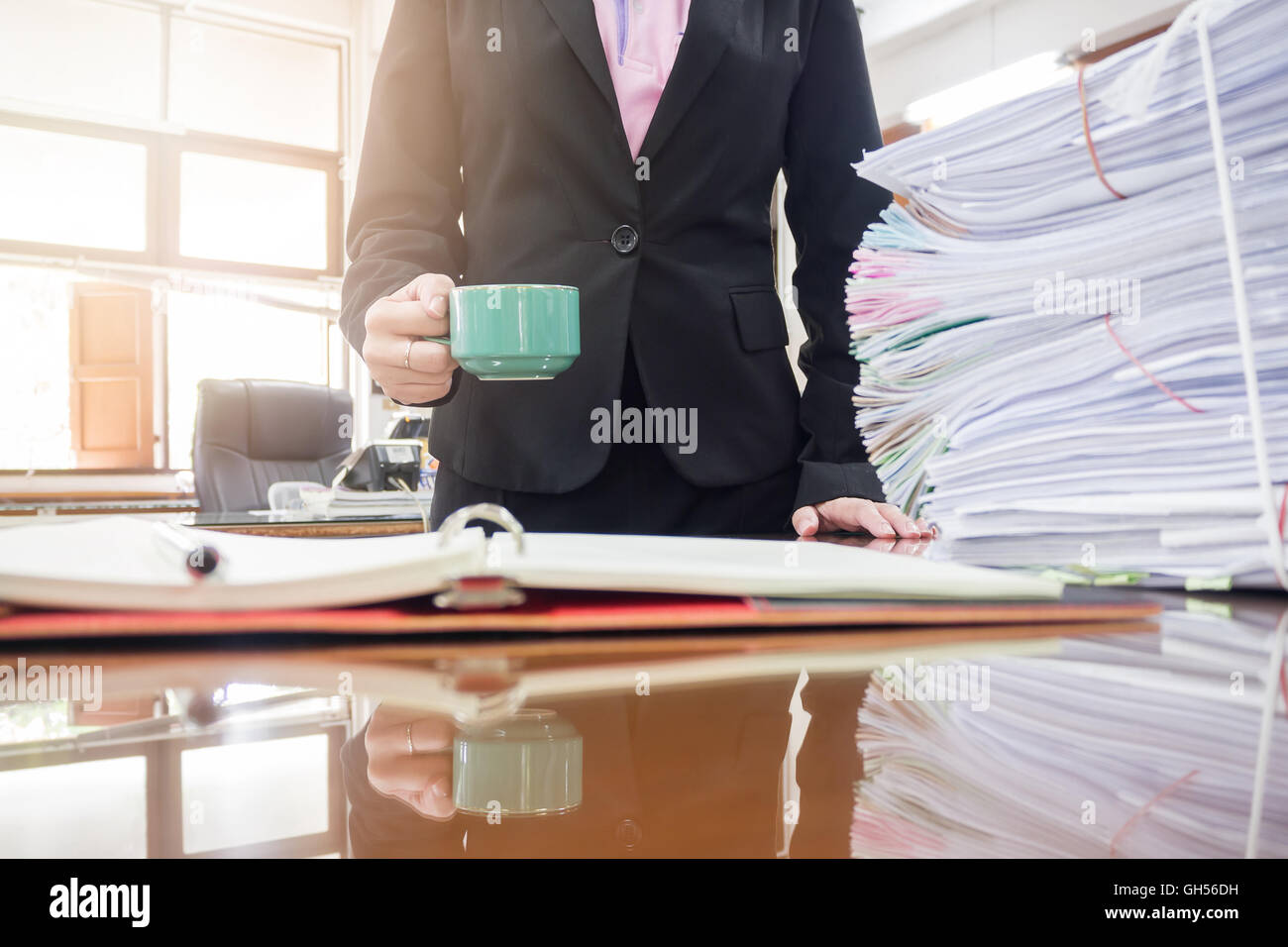 Businesswoman holding coffee cup in office - Stock Image