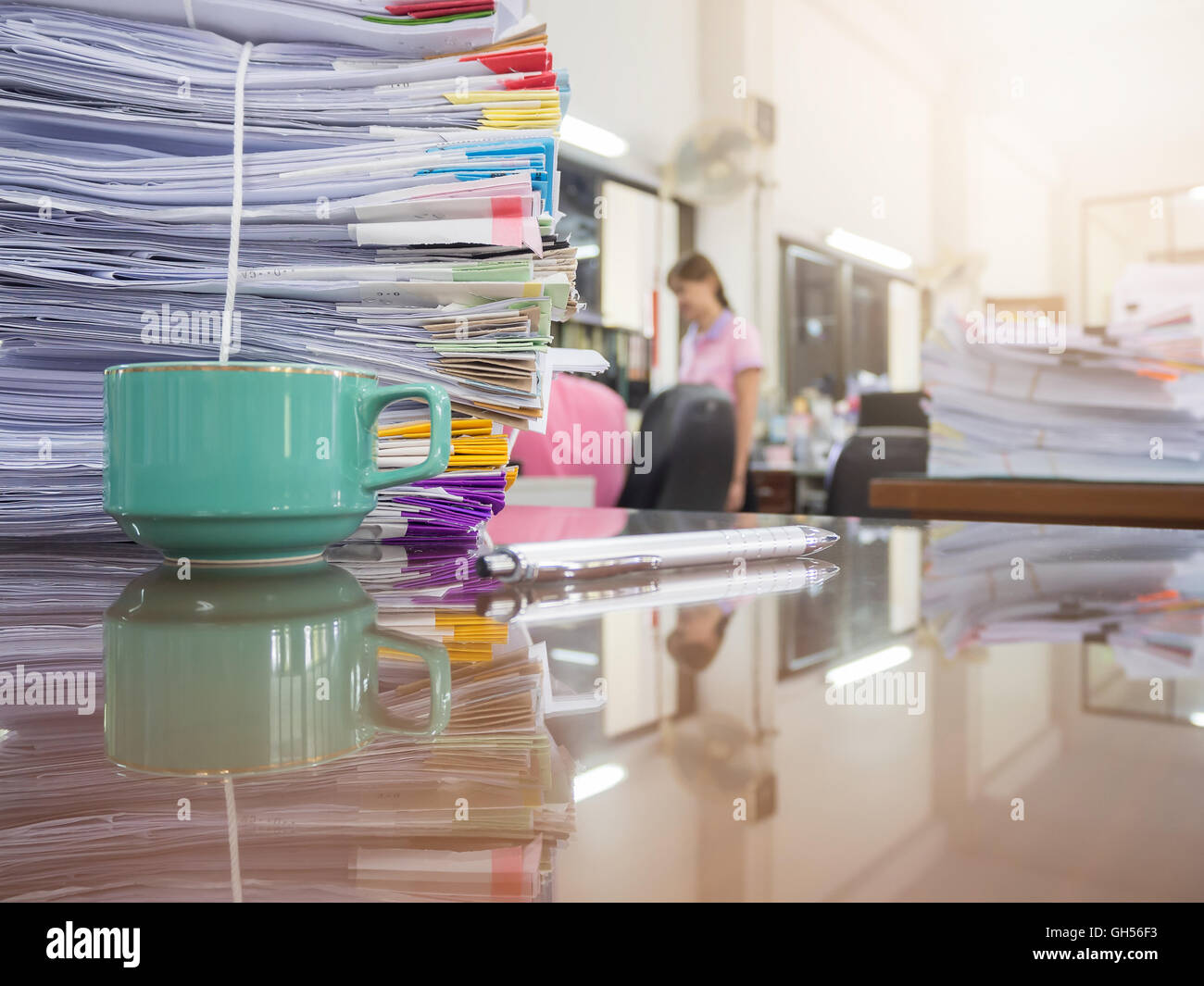 Pile of unfinished documents on office desk with businesswoman background - Stock Image