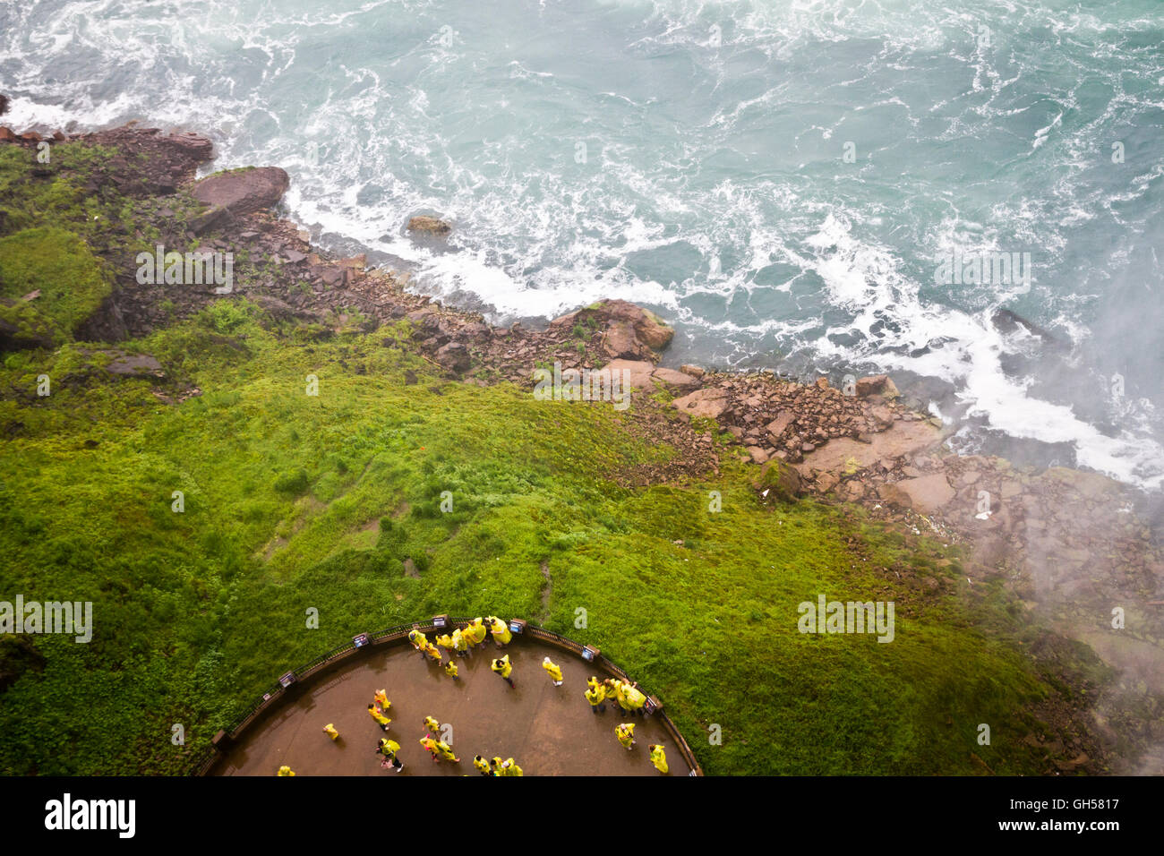 Tourists wearing yellow ponchos look out at the falls from a water-level platform at Niagara Falls, Canada. - Stock Image