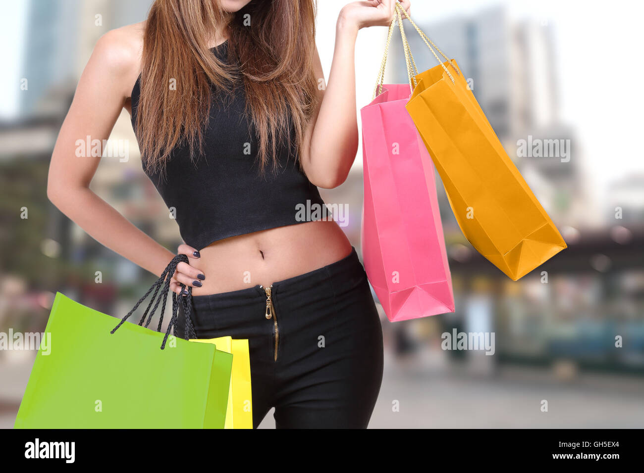 woman holding shopping bag and go shopping with blurred background - Stock Image