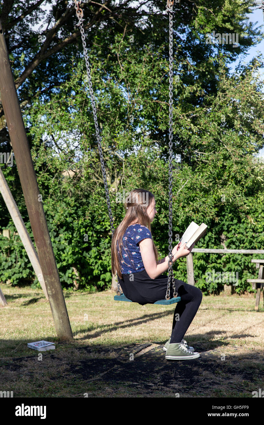 Girl reading in village park, child, park, black, meadow, trees, friends, relationship, boy, front, girl, relaxation, Stock Photo