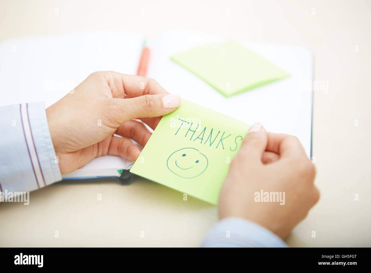 Hands of woman holding sticky note with Thanks text Stock Photo