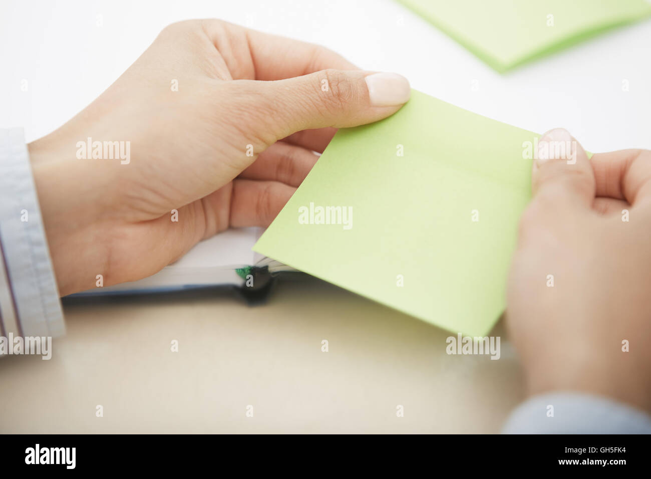 Hands holding green sticky note with empty space Stock Photo