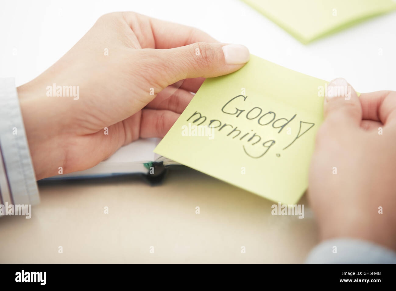 Hands holding sticky note with Good morning text Stock Photo