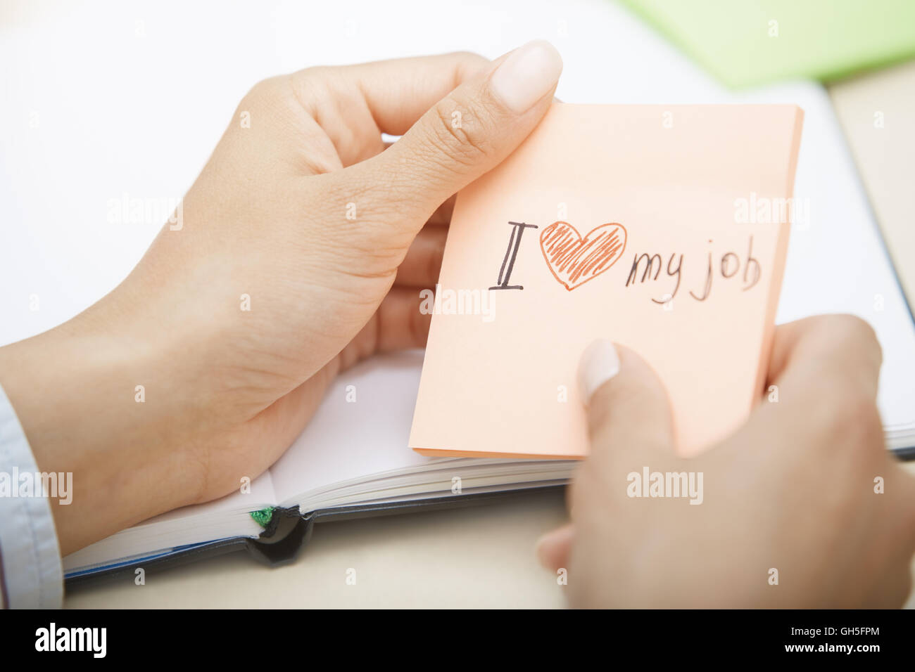 Hands holding sticky note with Love my job text Stock Photo
