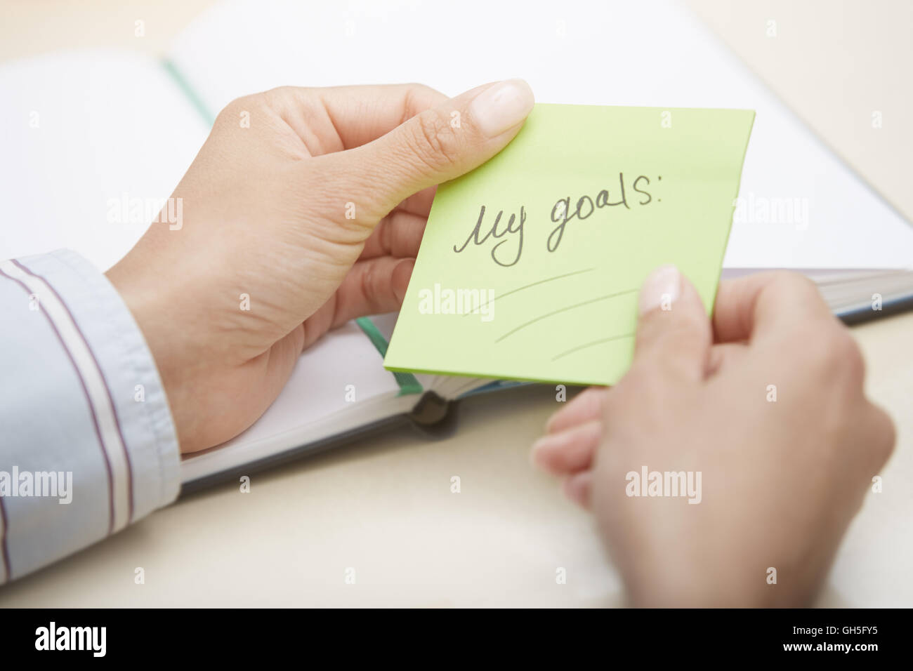 Hands holding green sticky note with planning of objectives Stock Photo