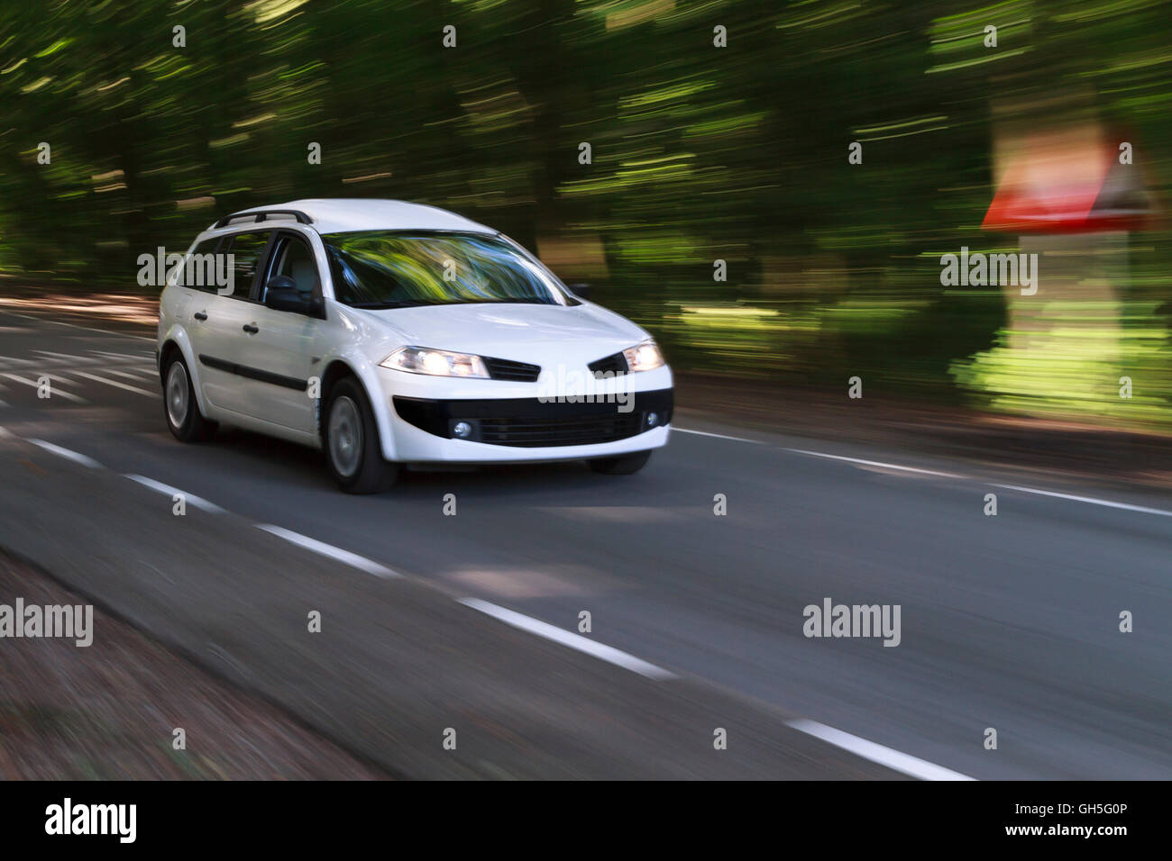 Speeding white car with motion look on a road coming out of the forest in the sunlight - Stock Image
