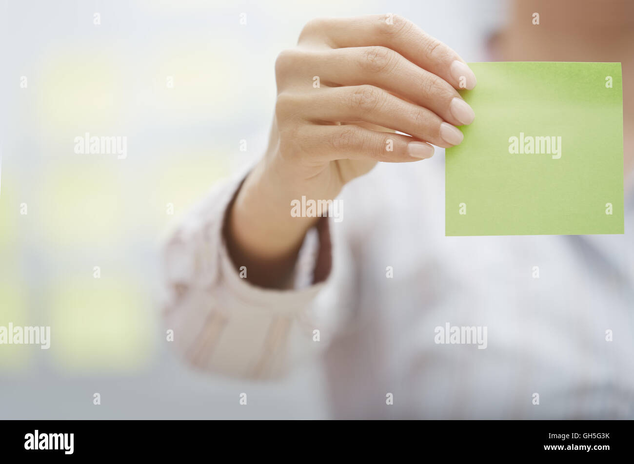 Woman holding sticky note with empty space Stock Photo